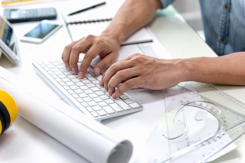 Designer at his desk using a computer keyboard